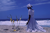 Rio de Janeiro, Brazil. New Year celebration at Macumba beach. Afro-brazilian woman ( voodoo priestess from Candomble religious rituals ). Palm flowers and bottles of drink in the beach sand. Offerings to Iemanjá, the Sea Goddess.