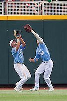 North Carolina outfielders Chaz Frank (2) and Skye Bolt (20) collide making a catch during Game 3 of the 2013 Men's College World Series against the North Carolina State Wolfpack at TD Ameritrade Park on June 16, 2013 in Omaha, Nebraska. The Wolfpack defeated the Tar Heels 8-1. (Andrew Woolley/Four Seam Images)
