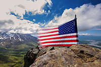 The American flag whips in the wind atop Lazy Mountain during a gorgeous summer day.  This strenuous hike provides pristine views of Alaska's Matanuska Susitna Valley.