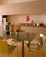The kitchen units display a geometric pattern in a 1970s theme matched by the containers on the glass table