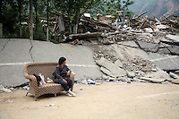 A woman sits on a wicker sofa on a destroyed road outside of Beichuan, Sichuan, China on 15 May 2008. China now estimates the death toll to be around 50,000 as prospects of survival for those still buried diminishes.