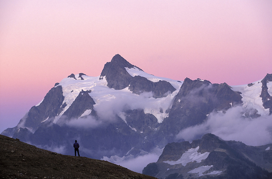 Hiker standing on ridge below Mt Shuksan at sunset, North Cascades, Cascade Mountains, Washington