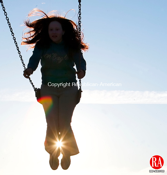 THOMASTON, CT- 29 MARCH 07- 032907JT10- <br /> Katie Nolte, 15, swings with the sunset behind her at the Black Rock School playground in Thomaston on Thursday.<br /> Josalee Thrift Republican-American