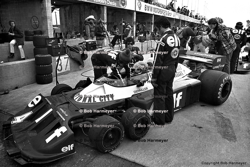 WATKINS GLEN, NY: A crew member tightens the safety belts of Patrick Depailler as he prepares to drive the  Tyrrell P34 7/Ford Cosworth DFV during a practice session for the United States Grand Prix East on October 2, 1977, at the Watkins Glen Grand Prix Race Course near Watkins Glen, New York.