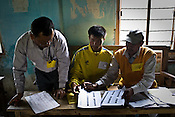 Government officials assist local villagers in casting their vote in a polling booth amidst high security in village Nungmaikhong, Manipur, India. About 62 per cent of 8,02,000 voters exercised their franchise in an incident-free secondphase of Lok Sabha elections for the prestigious Inner Manipur parliamentary constituency on April 22nd 2009.