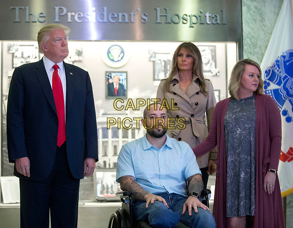 US President Donald J. Trump (2-L), with First Lady Melania Trump (3-R), listen as a citation is read for Sergeant First Class Alvaro Barrientos (3-L), with his wife Tammy Barrientos (2-R), during a Purple Heart ceremony at Walter Reed National Military Medical Center in Bethesda, Maryland, USA, 22 April 2017. Sergeant First Class Alvaro Barrientos was recently injured in Afghanistan while deployed and for the wounds he sustained, he is receiving the Purple Heart.<br /> CAP/MPI/RS<br /> &copy;RS/MPI/Capital Pictures