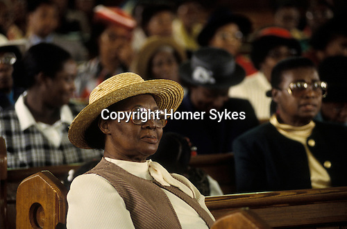 Church  of God of Prophecy west London. A  member of the congreation listens to the Sunday sermon. from A STORM IS PASSING OVER a Look at Black Churches in Britain. Published by Thames and Hudson isbn 0 500 27826 1