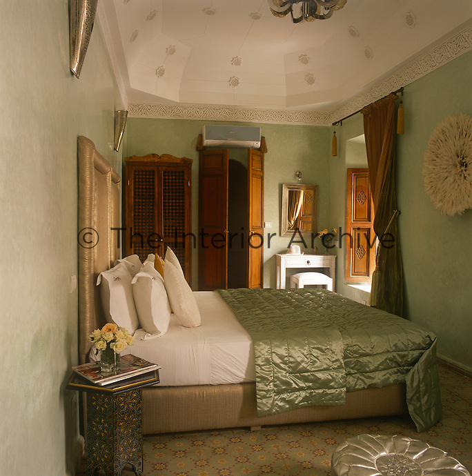 A guest bedroom decorated in tones of green with a high domed ceiling, built in cupboard and double bed.