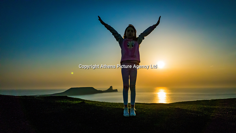 WEATHER PICTURE WALES<br /> The silhouette of a young girl raising her arms in the air as the sun sets over Worms Head at the end of a warm sunny day in Rhossili, Gower Peninsula, Wales, UK.