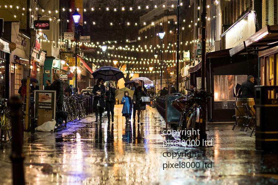 Pic shows: Wet weather brought out the colours of these Christmas decorations in Exmouth Market, London, E.C.1 last night.<br /> Young girl dressed up for a Christmas shopping outing with her family looked pretty as a picture in her blue coat.<br /> <br /> <br /> <br /> <br /> picture by Gavin Rodgers/ Pixel