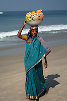 A woman carries a bowl of tropical fruit on her head in Goa, India, hoping to sell it to passers-by.