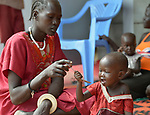 A mother feeds her child as part of a supplemental feeding program for malnourished children and mothers run by the clinic of the Loreto School in Rumbek, South Sudan. The school is run by the Institute for the Blessed Virgin Mary--the Loreto Sisters--of Ireland.