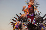 As the sun sets,a dancer in the men's  Northern Plains traditional category enters the Crow Fair dance arena in regalia including beadwork, feathers, quills, leather and paint.