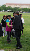 United States President Barack Obama (right) greets tourists from China as he walks from the White House to the United States Department of the Interior to sign an Executive Order, Wednesday, May 21, 2014 on the Ellipse in Washington, DC.<br /> Credit: John Harrington / Pool via CNP