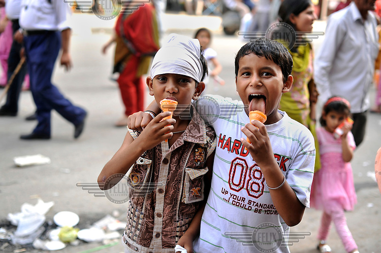 Young boys eat ice creams close to the Golden Temple complex in the Old City area of Amritsar.  .