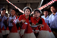 'Twin Teachers' Rian and Rossy slice the first rice cone to be given to students during Indonesia's Independence Day celebration at the school in North Jakarta. Since the early 1990s, twin sisters Sri Rosyati (known as Rossy) and Sri Irianingsih (known as Rian) have used their family inheritance to set up and run 64 schools in different parts of Indonesia, providing primary education combined with practical skills to some of the country's most deprived children.