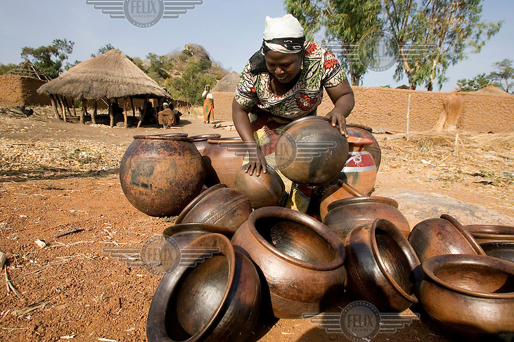 A woman makes a display with clay pots that she is selling beside a road.