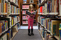 LOCKPORT, NEW YORK -  Jan 9: Katherine Miner, 9, reads a book in the children's section of the Lockport Public Library on Saturday, January 9, 2010 in  Lockport, New York. Katherine came to the library with her brother Jared, 9, and her father, Wes, to choose some books to check out and take home. (Photo by Landon Nordeman)
