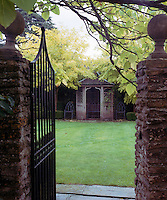 Green-painted metal gates open onto a charming walled garden, lawn and summer house