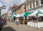 People shopping in busy pedestrianised street with market stalls in Winchester, Hampshire, England, UK