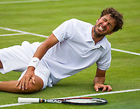 London, England, 30 june, 2016, Tennis, Wimbledon, Robin Haase (NED) falls to the grass in his match against Jack Sock (USA) and grabs his knie<br /> Photo: Henk Koster/tennisimages.com