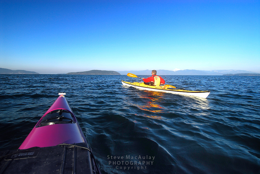 Male paddler in yellow kayak and yellow PFD paddling in San Juan Islands, Sea Kayaking the San Juan Islands, WA.
