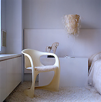 A designer chair by Steen Ostergaard sits in front of the bedside table with a small sculpture of a horse and a lamp with a feather shade by Steven Wine