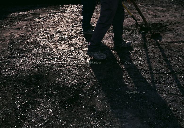 Shadowy figures of miners are cast on the blackened floor of a coal seam. Small mountaintop removal site employes a small number of workers that are cleaning up what a large company left as rubble.