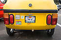 A rear view of yellow CityEl three-wheel electric car (manufactured by CityCom AG) with a 'LEMN WEJ' (Lemon Wedge) license plate. The phrase refers to the shape and color of the car. Electric Vehicle Rally in Palo Alto, hosted by the Silicon Valley Chapter of the Electric Auto Association, Palo Alto, California, USA