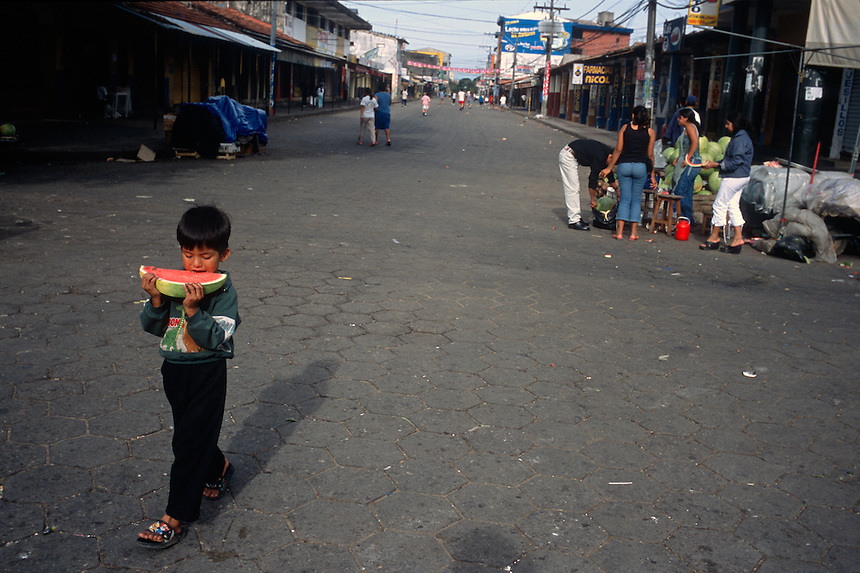 """A young boy walks with a fresh slice of melon in Santa Cruz de la Sierra, Bolivia Thursday, Nov. 11, 2004. Ernesto """"Che"""" Guevara was captured by the Bolivian army in 1967 in a nearby valley and executed in La Higuera days later. His body was put on public display in the laundry room of the Vallegrande hospital, then secretly buried under the air strip for 30 years. Guevara and fellow communist guerillas were attempting to launch a continent-wide revolution modeled on Guevara's success in Cuba in the late 1950s. The Bolivian government recently began promoting the area where he fought, was captured, killed and burried for 30 years as the """"Ruta del Che,"""" or Che's Route. (Kevin Moloney for the New York Times)"""