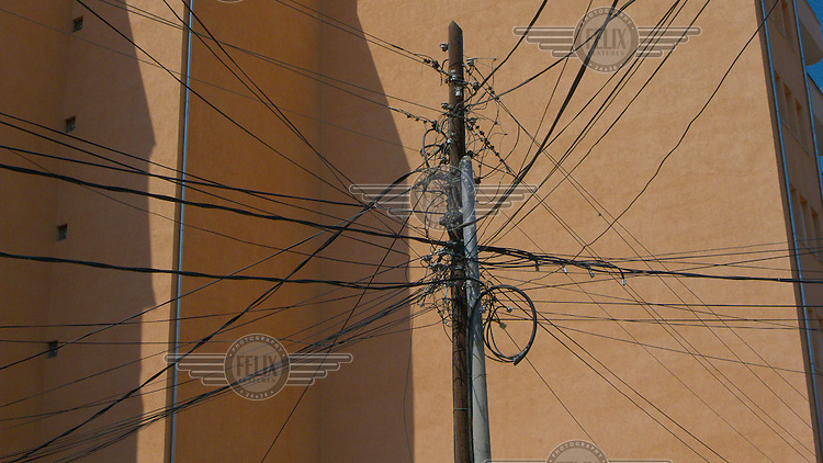 An overloaded electricity pylon next to a new apartment block in Prishtina.