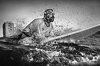 Surfer Awad Hania through the waves while paddling out into the Mediterranean Sea from Gaza City.