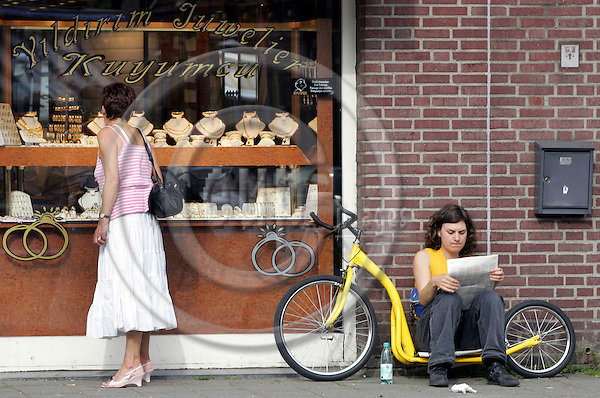 """EINDHOVEN - NETHERLANDS - 04 MAY 2006 -- Street sceene on the Kruisstraat in Eindhoven. A young woman resting on a """"kick-bicycle"""". -- PHOTO:  EUP-IMAGES / JUHA ROININEN"""