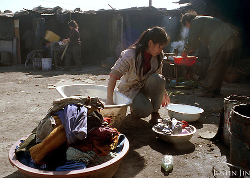 Li, the wife of the garbage dump manager Chen, washes clothes in the courtyard ringed by the workers' living quarters...Picture taken March 1999.Copyright Justin Jin