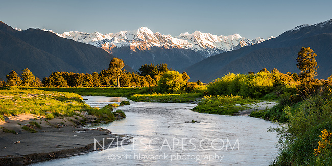 Sunset over farmland and Waitangitaona River and Southern Alps, West Coast, South Westland, New Zealand