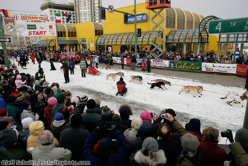 A crowd watches Deborah Bicknell leave the start line in Anchorage on Saturday March 1st during the ceremonial start day of the 2008 Iidtarod Sled Dog Race.