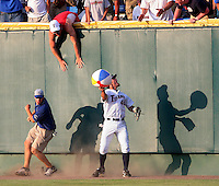 Cal State Fullerton right fielder Nick Mahin beats Rosenblatt grounds crew member Nick Svoboda to a beach ball and returns it to the fans during a 2007 College World Series game against Oregon State. Outfielders who return the ball to the bleachers become fan favorites since the grounds crew seize the balls and pop them. (Photo by Michelle Bishop)