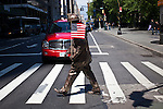 A man disguised as bronze statue workers walks at Lower Manhattan in New York, United States. 5/4/2012.  Photo by Eduardo Munoz Alvarez / VIEWpress.