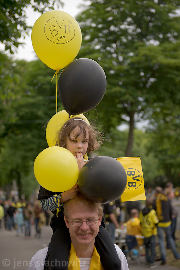A father humps his young daughter with her ballons in the club colors yellow and black. - In Dortmund fans celebrated a gigantic party because of the title win of their favorite soccer club BVB 09 in the German Premium League.