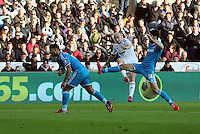 SWANSEA, WALES - FEBRUARY 07: Jonjo Shelvey of Swansea (C) crosses the ball over Patrick Van Aanholt (L) and Jordi Gomez (R) of Sunderland during the Premier League match between Swansea City and Sunderland AFC at Liberty Stadium on February 7, 2015 in Swansea, Wales.