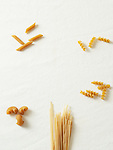 Different shapes of dry pasta on a white background.