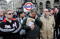 People, one with a copy of the Financial Times and another smoking the butt of a cigar, watch the demonstration outside the Bank of England. Thousands of protestors descended on the City of London ahead of the G20 summit of world leaders to express anger at the economic crisis, which many blame on the excesses of capitalism..