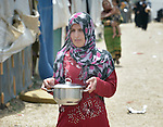Zahra Al Hussein carries a pot of soup to her tent  in a settlement of Syrian refugees in Minyara, a village in the Akkar district of northern Lebanon. Lebanon hosts some 1.5 million refugees from Syria, yet allows no large camps to be established. So refugees have moved into poor neighborhoods or established small informal settlements in border areas. International Orthodox Christian Charities, a member of the ACT Alliance, provides a variety of support for families in this settlement, including some meals--including this one--prepared in a community kitchen. Al Hussein is originally from the Syrian city of Homs.