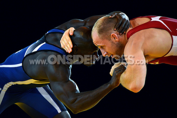 Melvin Bibo of Nigeria (blue) in action against Chris Laverick of Canada in the Men's 74kg freestyle Wrestling. Day six, Glasgow 2014 Commonwealth Games, Wrestling, on July 29, 2014 at SECC Precinct in Glasgow, Scotland. Photo by: Patrick Khachfe / Onside Images