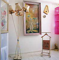 An eclectic arrangement of items stands in the corner of a room, including a standard lamp with four shades, a valet stand and artworks. The colour pink links the items together.