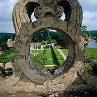 View through a circular stone carving on the roof of Longleat to the formal garden leading to the orangery