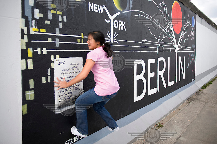 A tourist at the East Side Gallery, site of the former Berlin Wall that separated East Germany from West Germany.