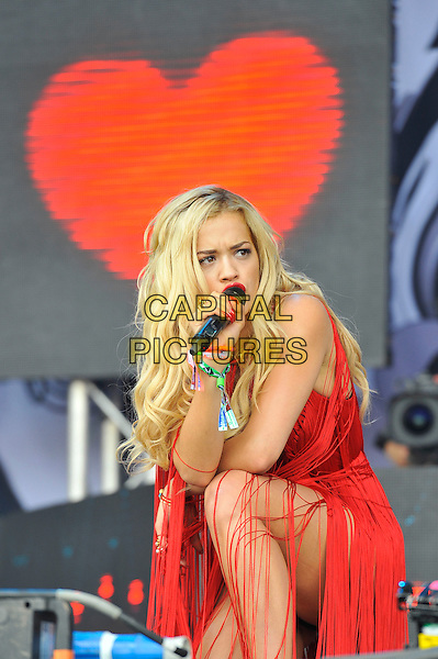 Rita Ora <br /> performing at Glastonbury Festival, Worthy Farm, Pilton, Somerset, <br /> England, UK, 28th June 2013.<br /> live on stage music gig half red tassels dress hotpants microphone black pants fringed singing <br /> CAP/MAR<br /> &copy; Martin Harris/Capital Pictures
