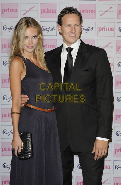 ZOE HOBBS & BRENDAN COLE .Comfort Prima High Street Fashion Awards 2010 at Battersea Evolution, London, England, September 9th 2010 half length black suit tie white shirt blue long navy maxi dress brown belt couple one shoulder clutch bag purple .CAP/CAN.©Can Nguyen/Capital Pictures.