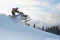Man driving his snowmobile through deep snow.